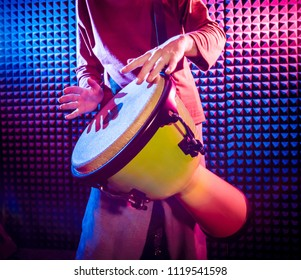 Young man playing on djembe in sound recording studio. African drums