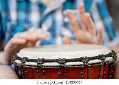 Young man playing on djembe. Shallow depth of field for emphasis on a musical instrument
