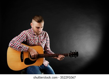 Young man playing on guitar on dark background