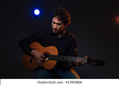 Young man playing on guitar over dark background
