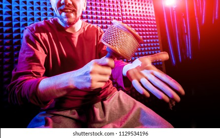Young man playing on maracas in sound recording studio. Modern background