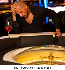 Young man playing roulette in casino betting and loosing