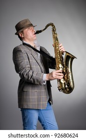 Young man playing the saxophone on a gray background.