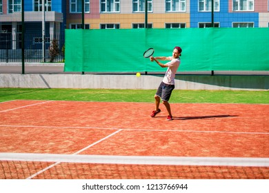 young man playing tennis on the court outdoor making a shot
