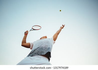 Young man playing tennis serving