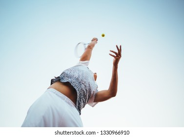 Young man playing tennis serving hitting the ball