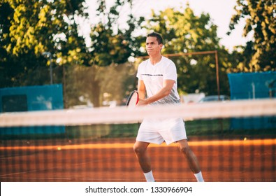 Young man playing tennis waiting at the net