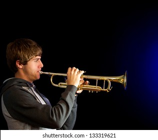 Young man playing a trumpet with a blue sound.
