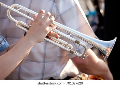 young man playing trumpet on street