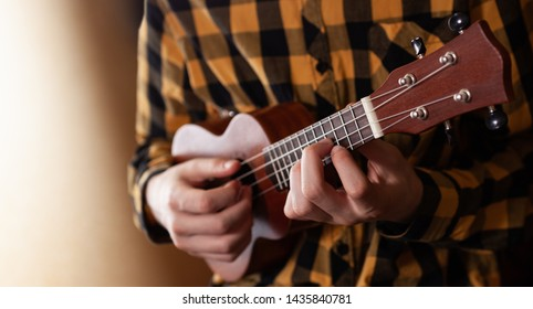 A young man playing ukulele in close up view
