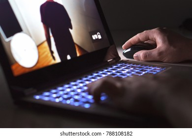 Young man playing video game with laptop. Gamer with computer in dark or late at night. Hands on mouse and keyboard. Competitive gaming, electronic sports and esports.