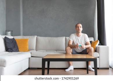 Junger Mann spielt zu Hause Videospiele. Glücklicher Kerl in Kausalkleidung sitzen auf einem großen Sofa mit Joystick in den Händen, kopieren Raum an Beton Wand.