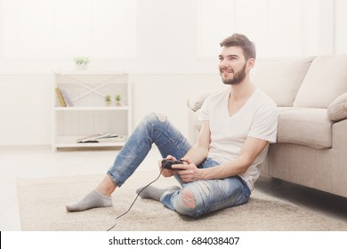 Young man playing video games at home. Happy guy sitting on the floor with joystick in hands, copy space