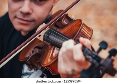 young man playing violin in the autumn forest.