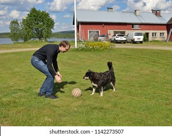 Young man plays with dog in ball