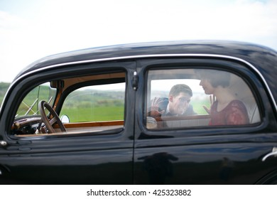Young man plays fool with a lady in vintage car