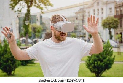 A young man plays a game wearing virtual reality glasses on the street. VR headset