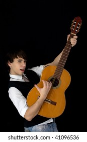 A young man plays guitar while holding it upwards