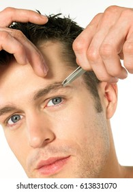Young man is plucking eyebrows with tweezers.