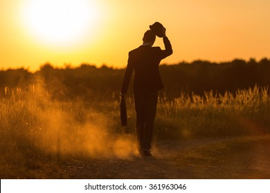 A young man with pocket and hat walks in the sundown