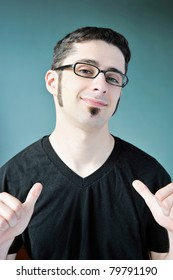 A young man pointing at himself with both thumbs.