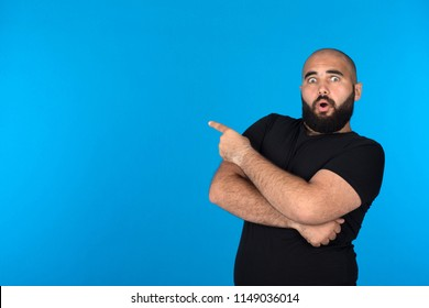 Young man pointing with one finger while crossed his arm looks surprised, on a blue background.