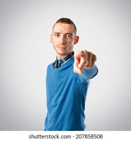 Young man pointing over isolated grey background