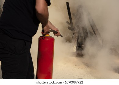 Young man pointing a powder type fire extinguisher forwards towards the fire in a serious situation
