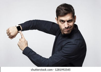 Young man pointing at watch with impatience as if asking to hurry up, isolated on gray background. It's time to act!