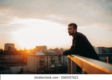 Young man is pondering on terrace of house roof against background of cityscape at sunset. Copy space.