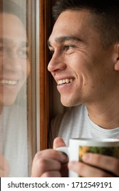 Young man portrait smiling looking out the window holding a hot drink cup. Window reflection image.