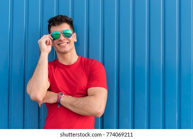 Young man posing in blue background with sunglasses