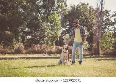 Young man posing with his canadian labrador dog in an urban park