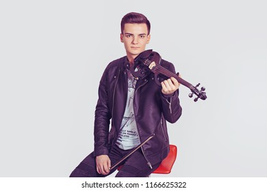 Young man posing holding modern violin and fiddle-stick smiling sitting on a red chair isolated on white wall background. Horizontal shot model in black leather jacket white shirt. Music passion hobby