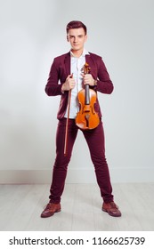 Young man posing holding modern violin and fiddle-stick standing in a room with light wall and floor. Vertical shot model in red burgundy classic suit white buttoned shirt. Music passion hobby concept