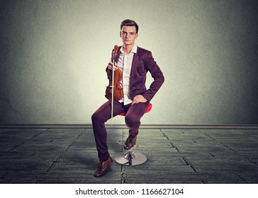 Young man posing holding modern violin and fiddle-stick sitting on a red in room with gray wall and floor. Vertical shot model in vinous burgundy classic suit white buttoned shirt. Music passion hobby