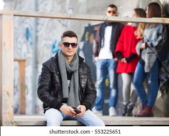 Young man posing outdoors and looking in to a camera