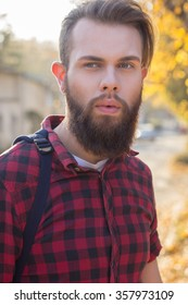 Young man posing in the street, fashion style, mustashe. Bearded hipster in the city outdoor