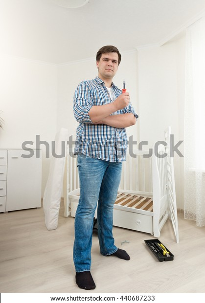 Young man posing with tools at disassembled baby bed at bedroom