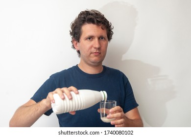 A young man is pouring dairy yogurt in a glass on a white background.