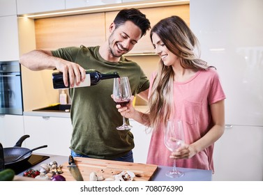 Young man pouring a glass of wine for his girlfriend in the kitchen, celebrating together