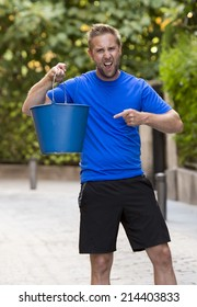 young man pouring ice water bucket on his head getting wet outdoors in internet viral media network challenge campaign to support degenerative sclerosis and neuronal disease and disorder