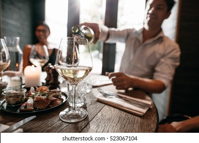 Young man pouring wine from the bottle into a glass with friends sitting around the table. Young people having wine at restaurant.