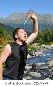 A young man pours water on his head from a plastic bottle, white mountain river, mountain top