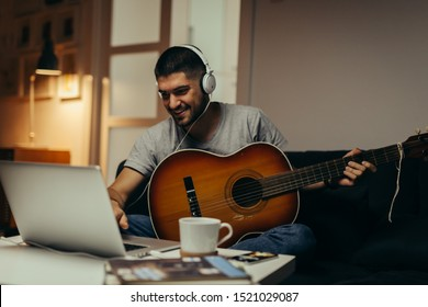 young man practice to play guitar at his home