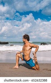 Young man practice yoga on the beach during retreat vacation in Bali, stretching, meditation, wellness
