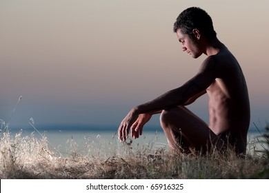 young man practices yoga at sunset on a steep beach