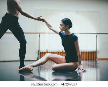Young man practicing in classical ballet with young beautiful woman in black clothing in the gym or ballet hall. Couple jumping dancing sensual dance. Minimalism interior,