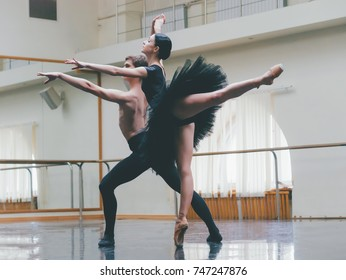 Young man practicing in classical ballet with young beautiful woman in black tutu clothing in the gym. Minimalism interior, dancing sensual dance.