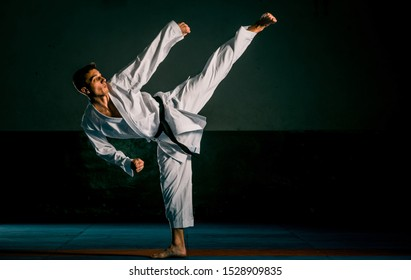 Young man practicing his karate moves, doing a high kick while standing still wearing white kimono and black belt